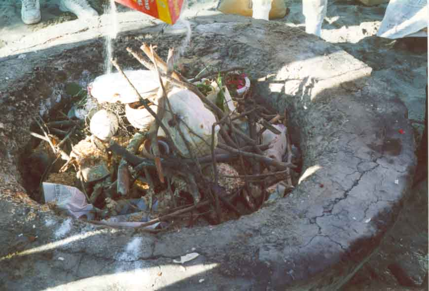 The pottery is carefully placed in the pit and wood chips and small branches are added