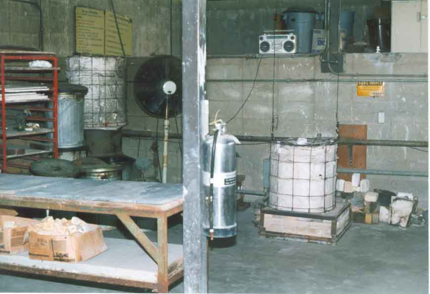 Raku kiln with surrounding area including fan, slate table, reduction containers, and fire extinguisher